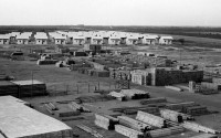Old black-and-white photo. In the background an army of small wooden houses, in the front stacks of wooden elements.