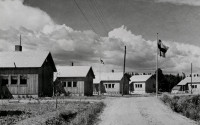 Old black-and-white photo, five wooden houses along a small gravel street, Finnish flag up in a flagpole.