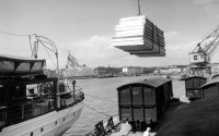 Old black-and-white photo, wooden elements being lifted from a train to a ship. Harbour crane in the background.