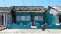 Facade of a small turquoise wooden house.