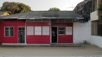 Facade of a small bright-red wooden house.