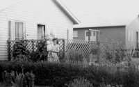 Old black-and-white photo. Two wooden houses, a lady with a child in her arms in front of one.