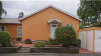 Gable of a small orange-yellow wooden house.